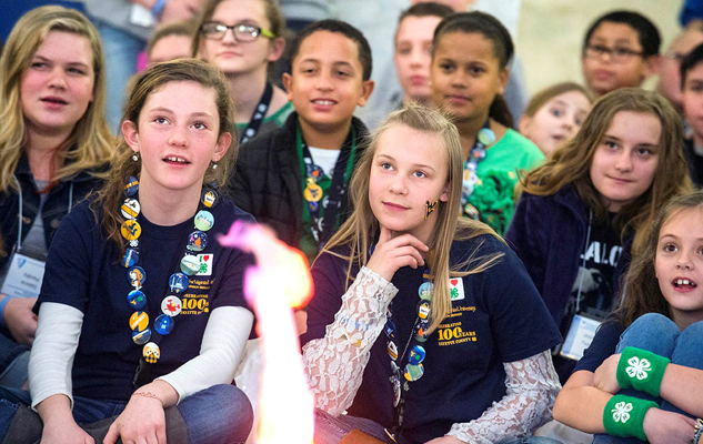 4-H members watching a fire with excitement